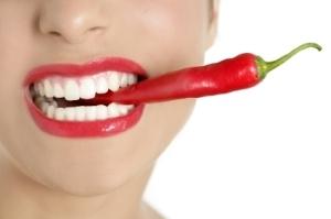 Beautiful woman teeth eating red pepper