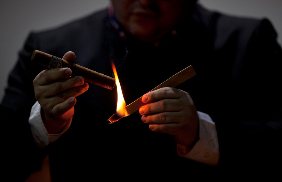 A man lights a cigar during the inauguration of the 15th Cigar Festival in Havana, Cuba, Tuesday, Feb. 26, 2013. Cigar enthusiasts from around the world come to Cuba during the annual celebration to visit tobacco farms and factories and savor new cigar brands. (AP Photo/Ramon Espinosa)