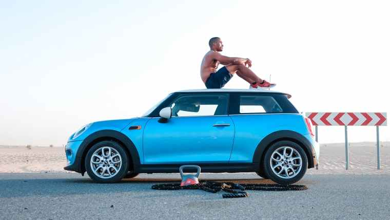 man sitting on blue mini cooper