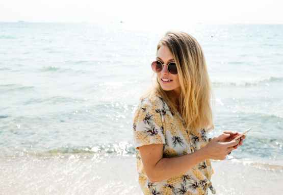 woman in black yellow and white floral button up shirt holding smartphone wearing aviator sunglasses near body of water