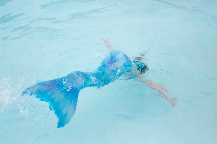 photo of woman with blue mermaid tail