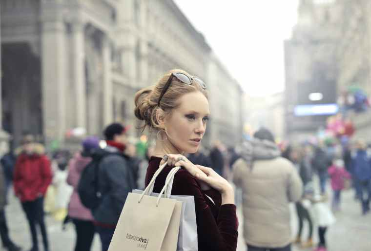 woman wearing maroon long sleeved top carrying brown and white paper bags in selective focus photography